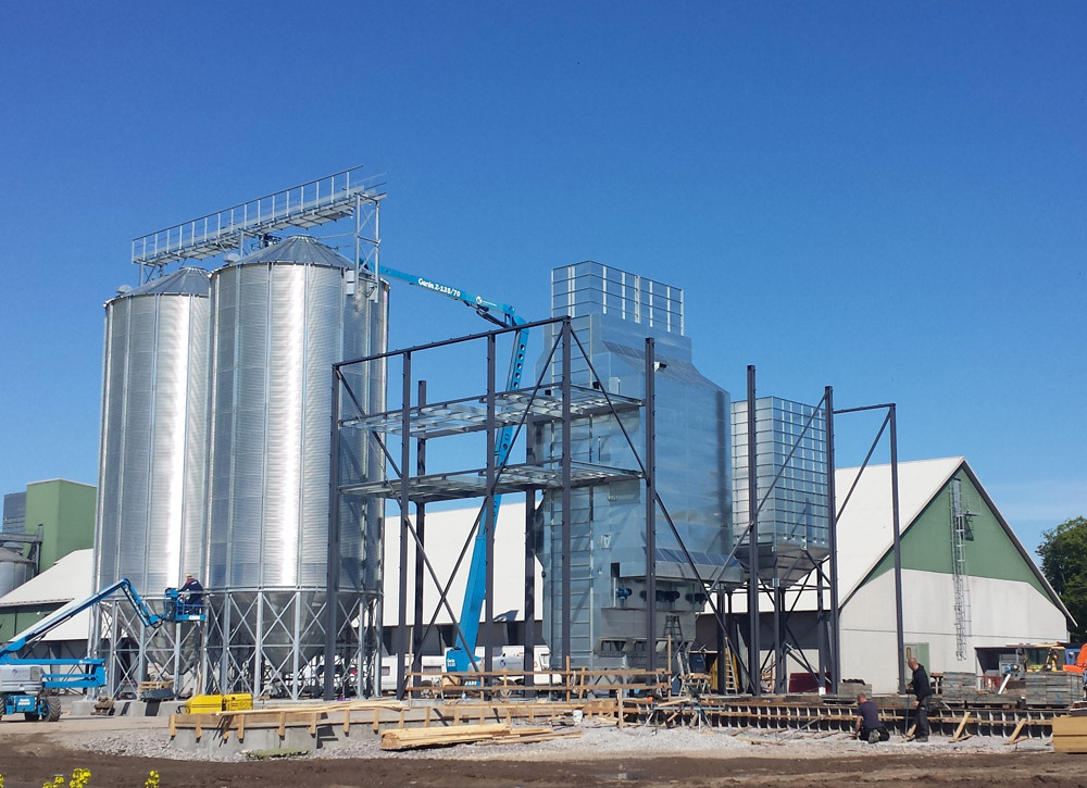 2014-05-15 The catwalk over the hopper silos is currently assembled and the hopper under the cylinder is on its place. All drying sections is assembled and the bulk loading bins is also on place.